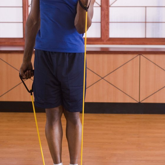 Resistance band curls target your biceps.