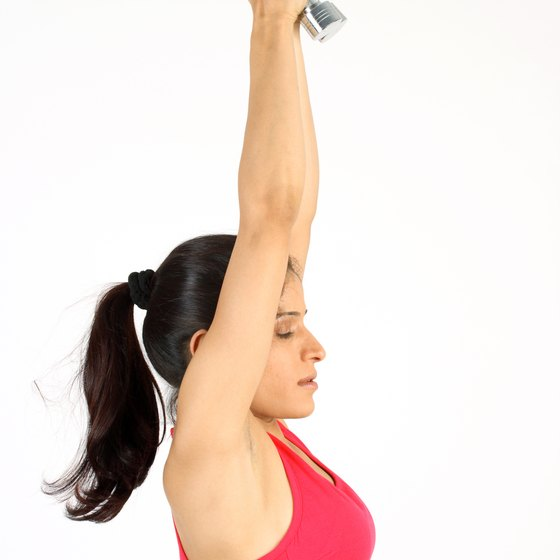 Use a hand weight to perform extensions that strengthen your lower back.