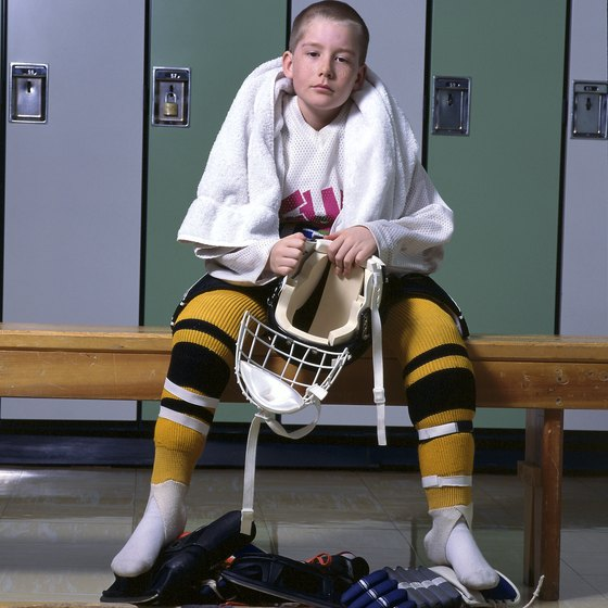 Players suit up in the dressing rooms before a hockey game.