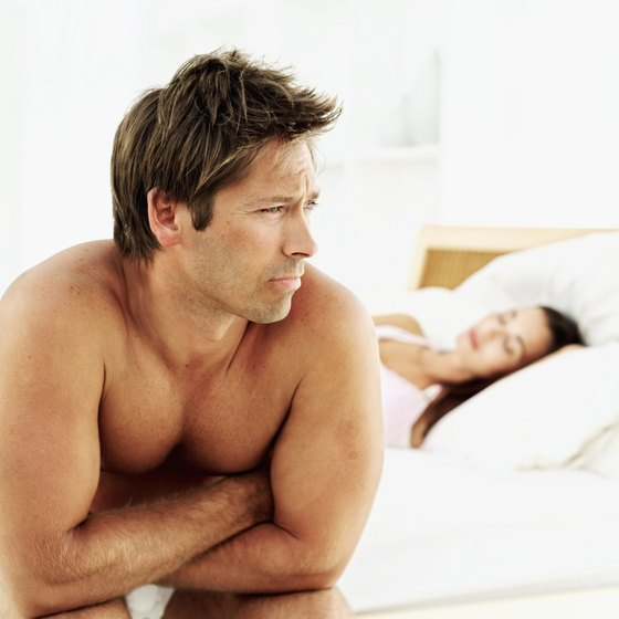 A man sits on a bed while his partner sleeps.