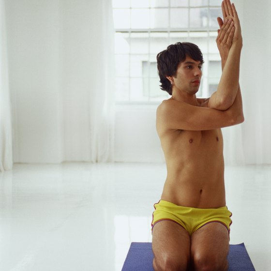 A man performing an Eagle arm twist during Bikram yoga.