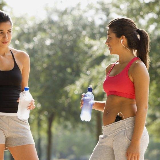Two women holding water bottles while on exercise break.