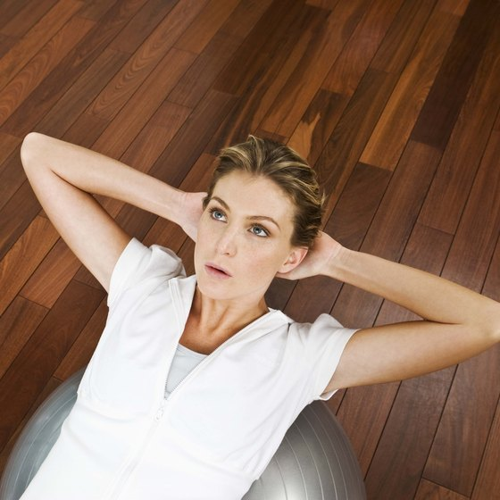 Crunches on an exercise ball help to engage abdominal muscles and tone your midsection.