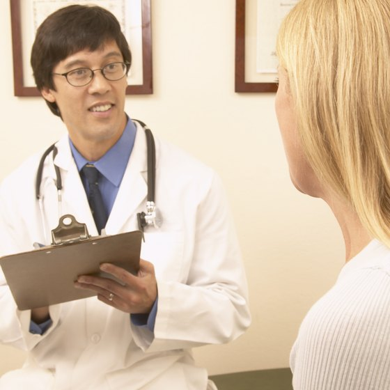 Doctor holds a clipboard while having a discussion with a patient.