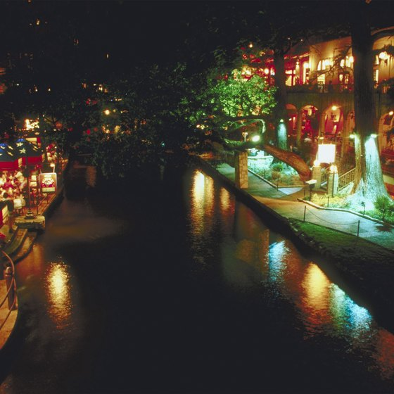 Twinkling lights cascading from cypress trees along the San Antonio River Walk create a romantic backdrop at night.