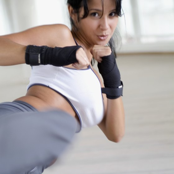 Keeping arms tense and ready to throw a punch during a kickboxing workout helps to tone arms and reduce flab.