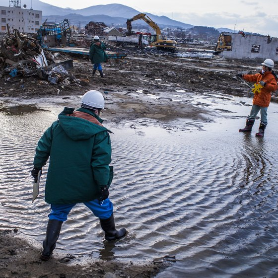 Two experts walk in the water at a site destroyed by an earthquake.