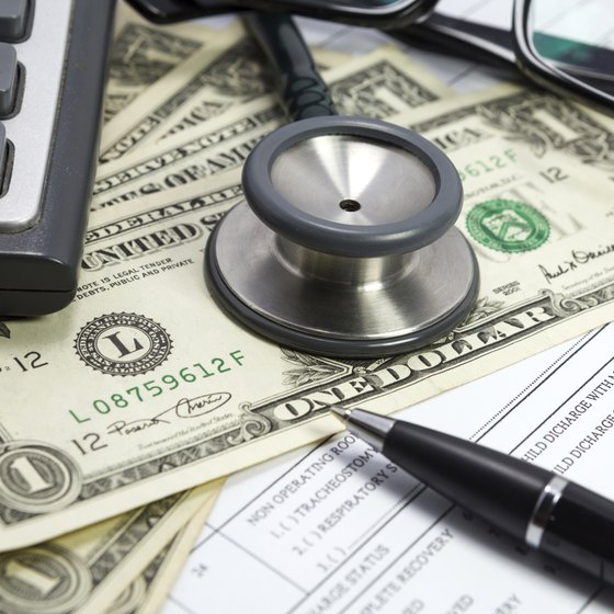 Close-up of stethoscope on top of medical billing papers and cash