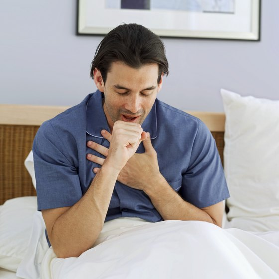 Man coughing in bed