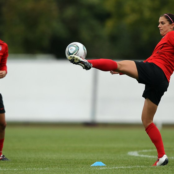 Alex Morgan, right, practices shooting during training for the U.S. national team.