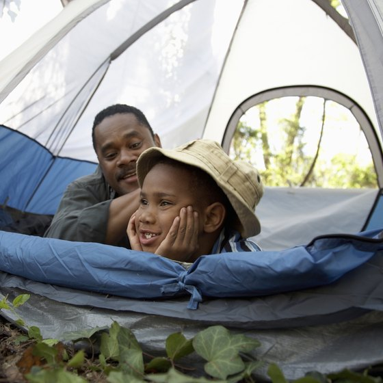 A father and child laying inside a tent.