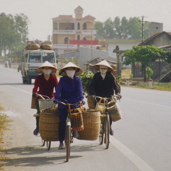 Vietnamese people still wear traditional hats when working.