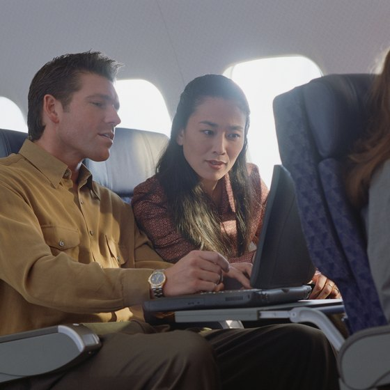 Couple on airplane looking at laptop