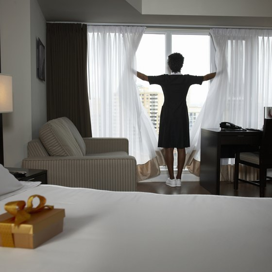Housekeeper opening curtains of room