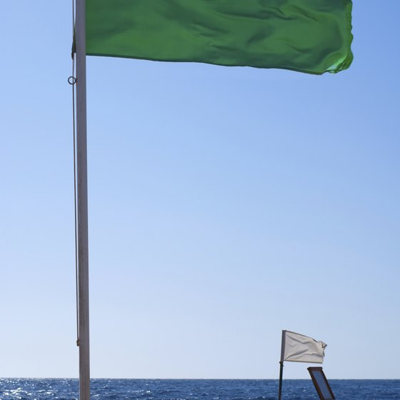 A white flag waves next to a sign on the beach.