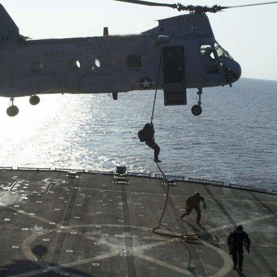 Navy SEALs rappell from a Sea Knight helicopter as part of a shipboard takeover exercise.