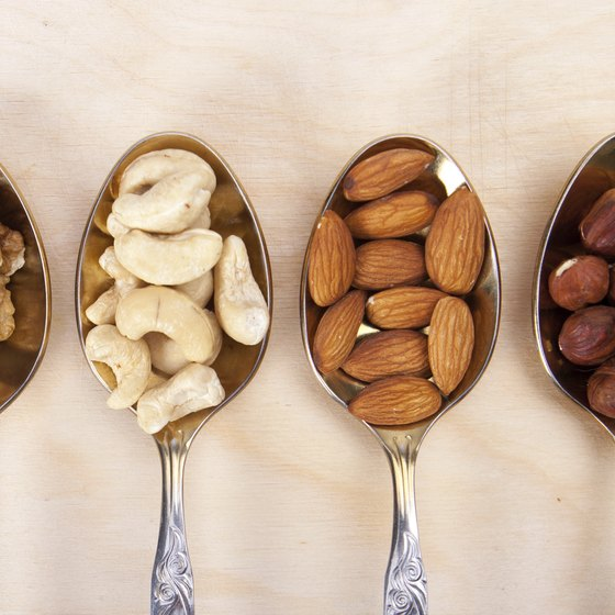 Spoons filled with different kinds of nuts.