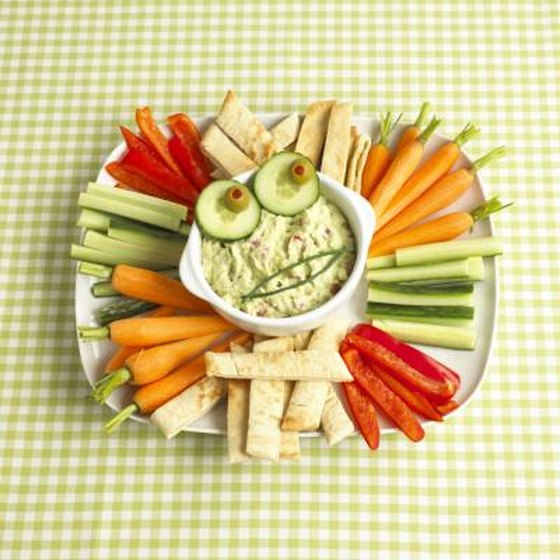 Bowl of guacamole surrounded by pieces of pita bread and raw vegetables