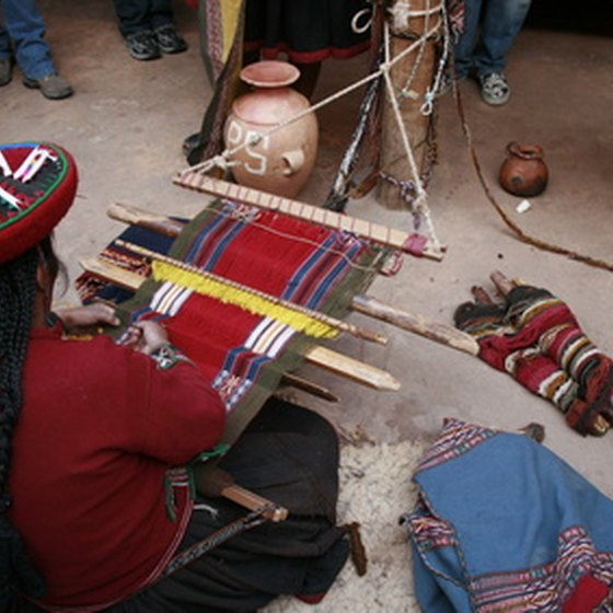 An indigenous woman weaving on a backstrap loom.