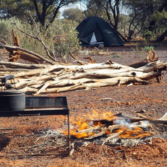 A hot meal being prepared by campfire.