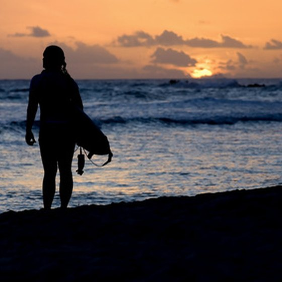 A surfer walks on the beach at sunset
