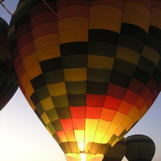 "Tethered hot air balloons are illuminated during a ""balloon glow."""