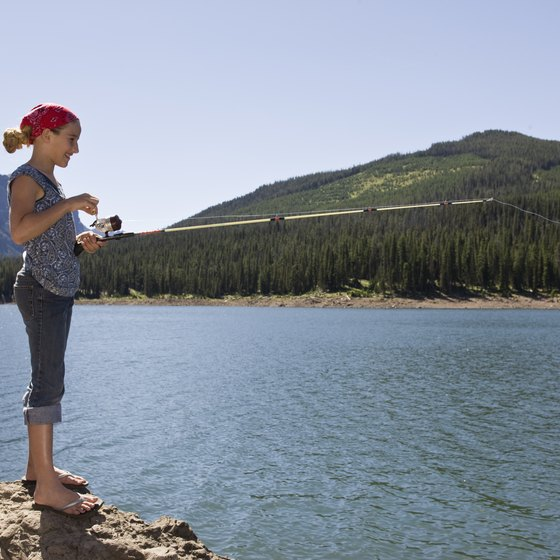 Teach children to fish on a mountain lake.