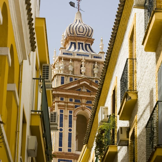 Narrow streets and ornate architecture can be seen in Seville, Spain.