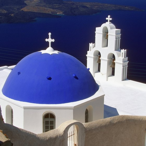 A church dome and bell tower overlooking the coast of Santorini.