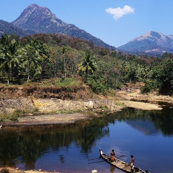 Native canoes share the waterways as you kayak through Kerala