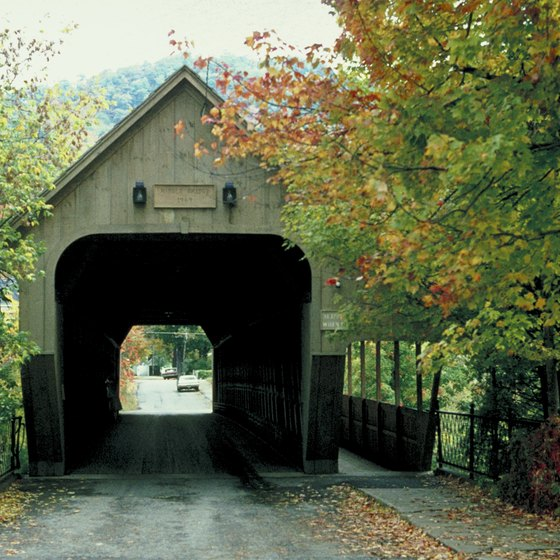 A covered bridge crosses the Ottauquechee River in Woodstock, Vermont.