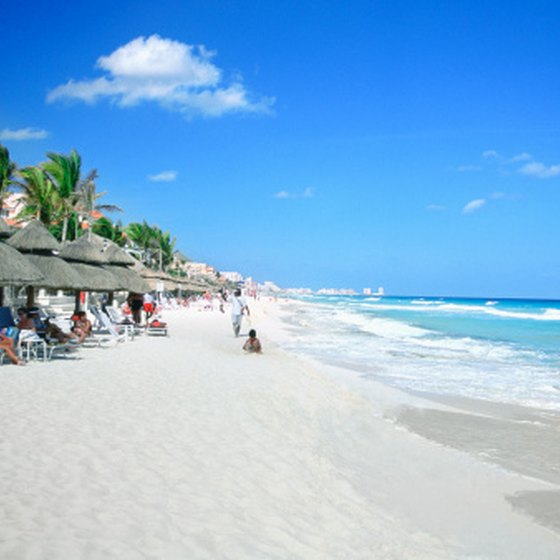 Let your baby explore Cancun's sandy beaches in a shaded area.