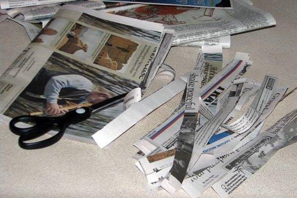 Corta el periódico con tijeras para hacer tiras.
