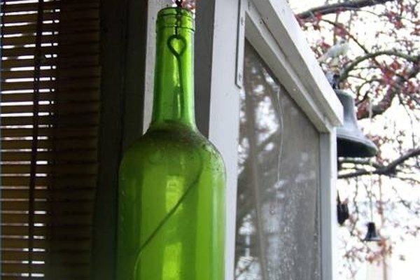 Cut a hole in a glass bottle and create a hanging display.