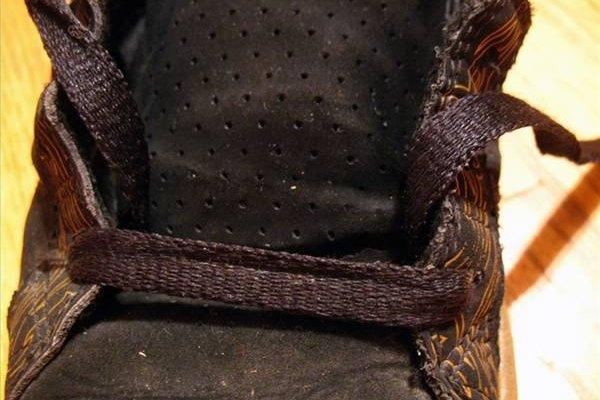 Pasa el cordón por los dos primeros orificios de abajo.