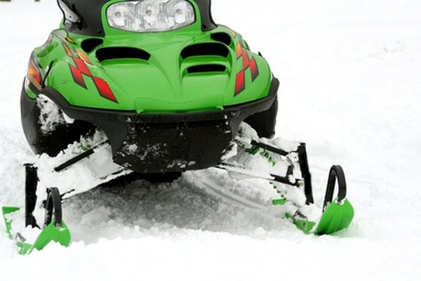 It's helpful to have an assitant when removing the track from a snowmobile.