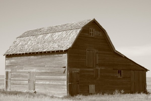 The photo of an old barn has been processed to have a reddish-brown sepia tint.
