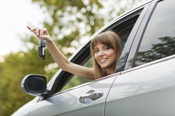 Woman holding the keys to a new car.