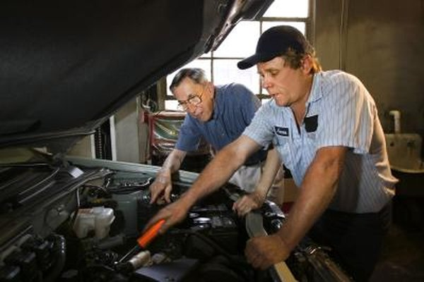 A man watches a mechanic work on his car's engine