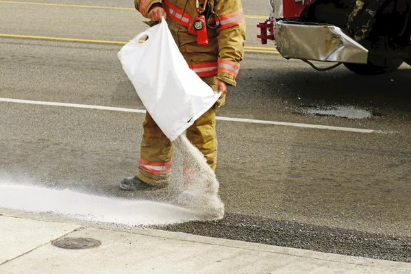A firefighter pouring an absorbant over a diesel fuel spill.