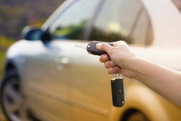 A close-up of a woman setting a car alarm with her key chain.