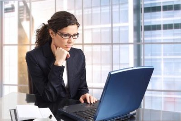 A businesswoman types on her laptop