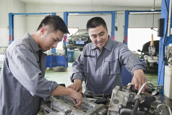 Two mechanics work on a car engine at an auto repair shop
