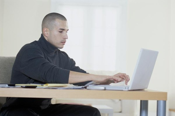 A man types on his laptop computer in his home office