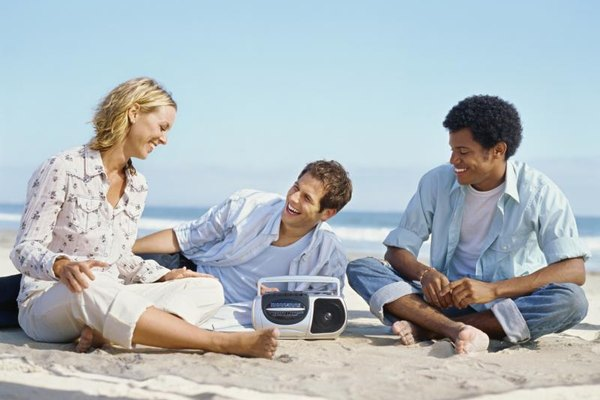 Two young men and a woman sitting on the beach listening to a radio.