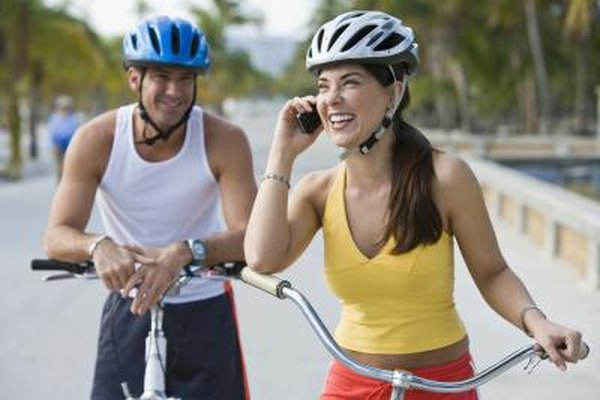 People on bikes using their cell phones.