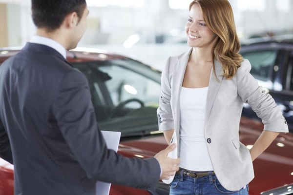 Car salesman talking to a young woman in front of a new car.