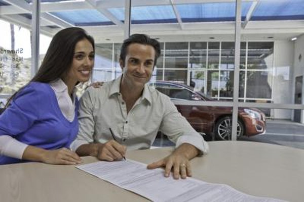 A married couple sign documents at a car dealership