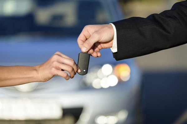 Salesman handing over key to a car