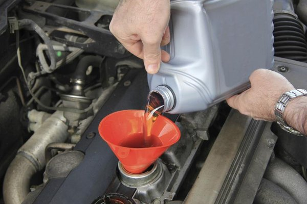 Pouring oil into the engine of a car.